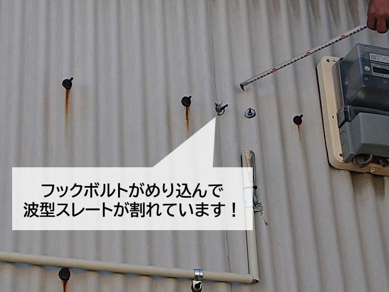 岸和田市の倉庫のフックボルトがめりこんで波型スレートが割れています