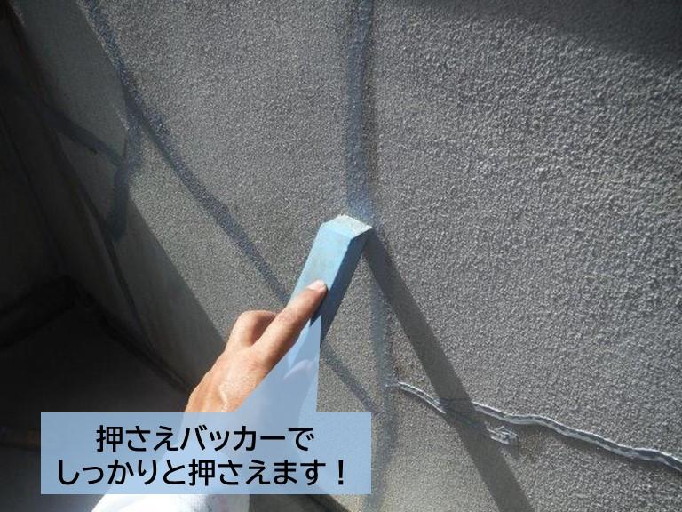 泉大津市のベランダの手すり壁のひび割れに充填したシーリングを押さえます