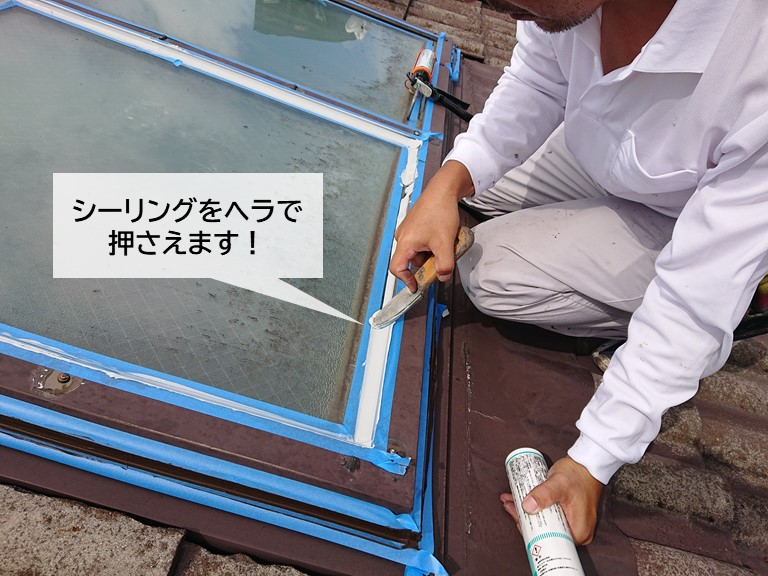 泉大津市の天窓のガラス周りに充填したシーリングを押さえます