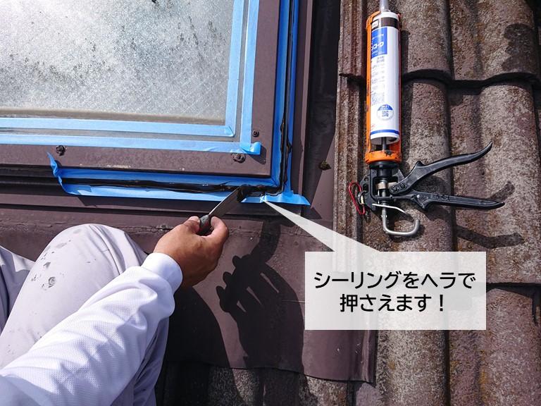 泉大津市の天窓の窓枠の取り合いに充填したシーリングをヘラで押さえます