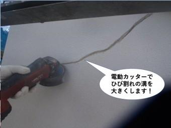 岸和田市の外壁に電動カッターでひび割れ面を広げます