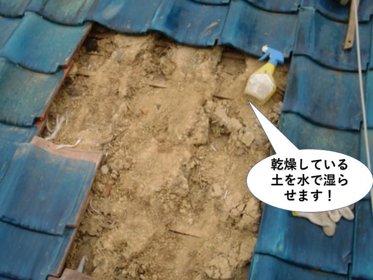岸和田市の屋根の乾燥している土を水で湿らせます