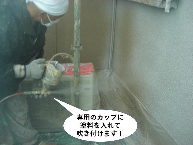 岸和田市の外壁に専用のカップに塗料を入れて吹き付けます