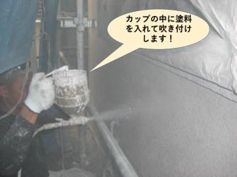 岸和田市の塗装でカップの中に塗料を入れて吹き付けします