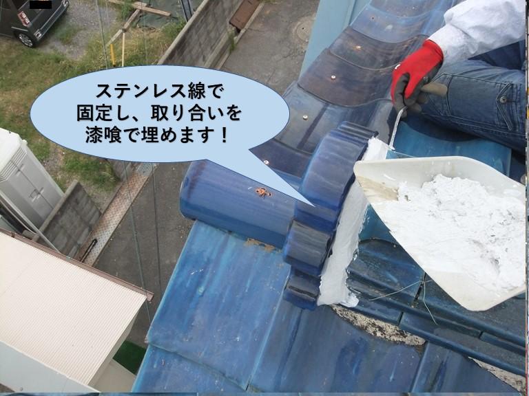 岸和田市の鬼瓦をステンレス線で固定し取り合いを漆喰で埋めます