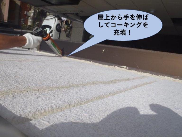 堺市のマンションの屋上から手を伸ばしてコーキング充填