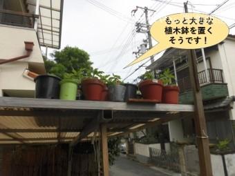 岸和田市のカーポートの屋根に大きな植木鉢を置きます