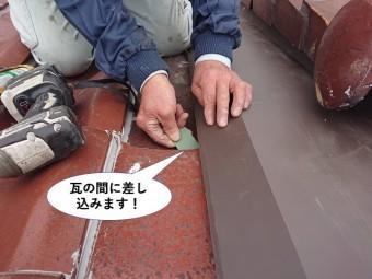 熊取町で細長い板金を瓦の間に差し込みます