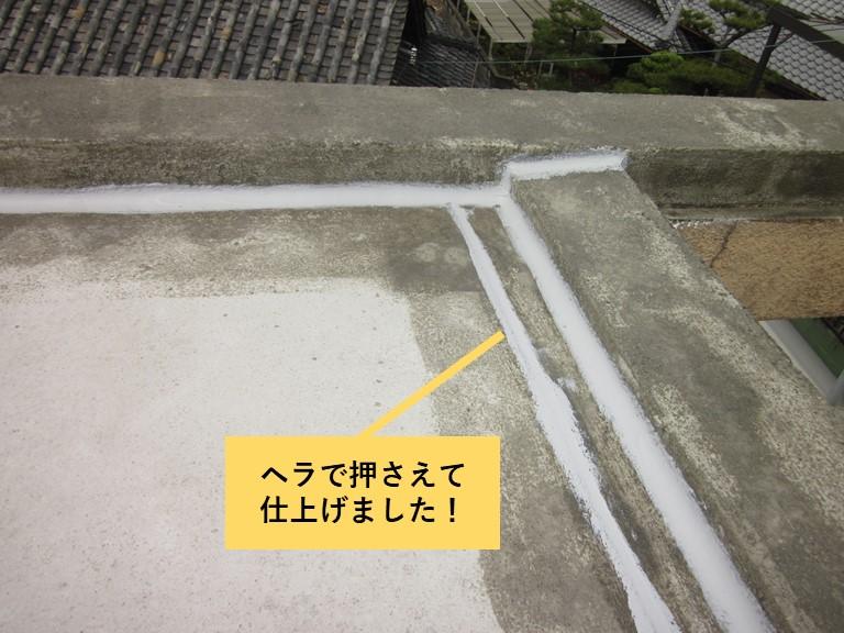 和泉市の陸屋根の目地に充填したシーリングをヘラで押さえました