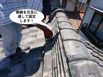 岸和田市の棟に銅線を交互に通して固定します