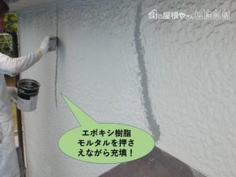 岸和田市の外壁のひび割れにエポキシ樹脂モルタルを押さえながら充填します