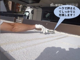 堺市のマンションのコーキングをヘラで押さえてしっかりと充填します
