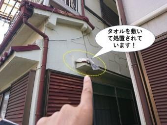 岸和田市の庇にタオルを敷いて処置されています