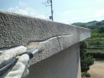 岸和田市包近町の屋根のクラックの溝を刷毛で清掃