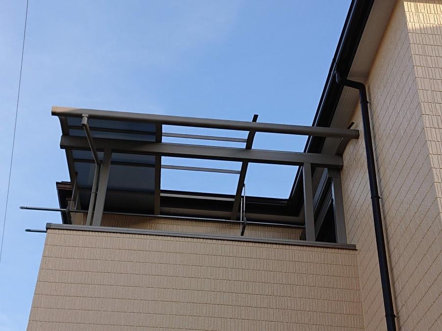 熊取町のベランダ屋根のパネルが飛ばされています