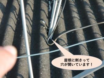 岸和田市の倉庫の屋根に刺さって穴が開いています