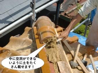 熊取町の冠瓦の中に空洞ができないように土をたくさん載せます