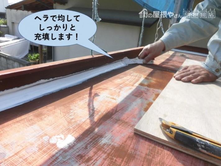 岸和田市の玄関庇の屋根に充填したコーキングをヘラで均してしっかりと充填します!