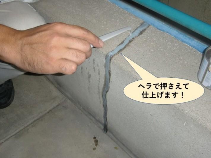 岸和田市のベランダのコーキングをヘラで押さえて仕上げます