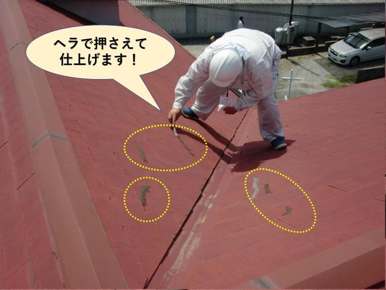 根のひび割れに充填したコーキングをヘラで押さえて仕上げます