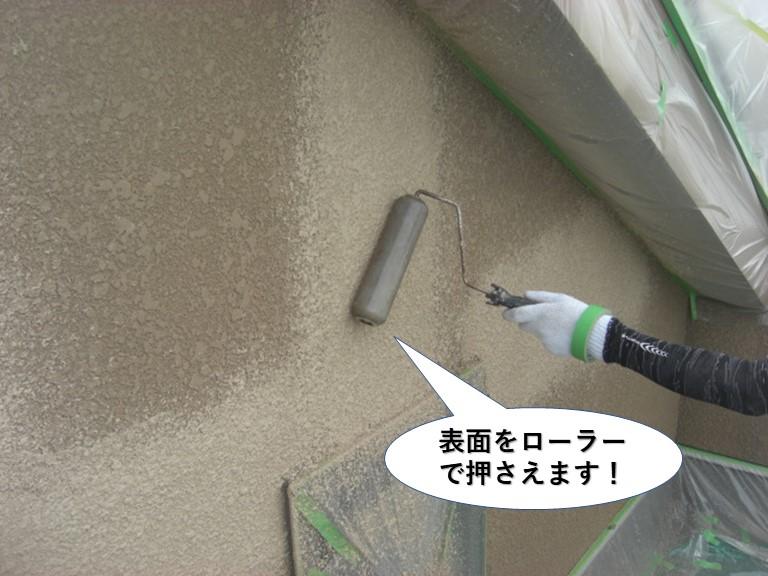泉大津市の外壁の塗膜の表面をローラーで押さえます