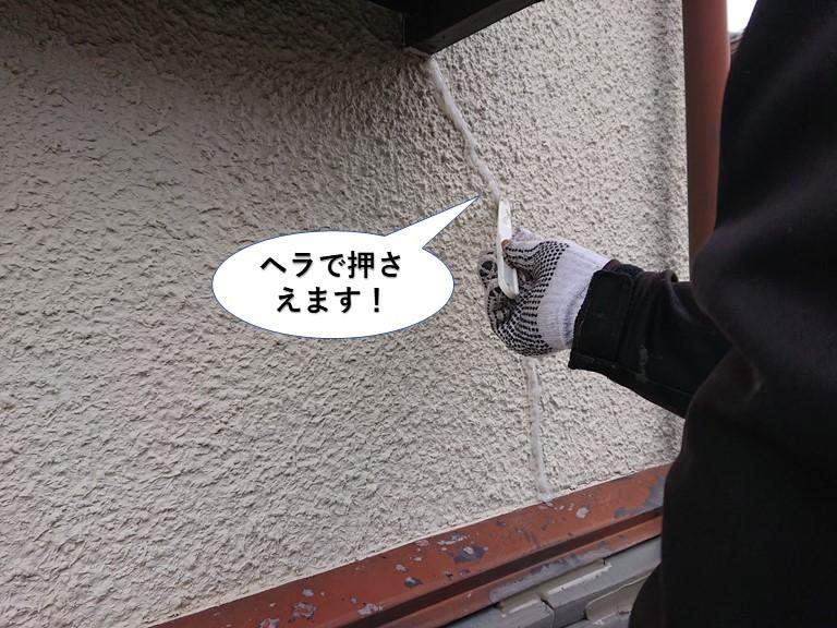 泉佐野市の外壁のひび割れに充填したシーリングをヘラで押さえます