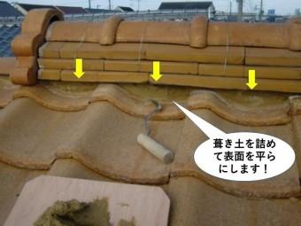 熊取町の棟に葺き土を詰めて平らにします