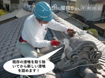 岸和田市の鬼瓦の取り合いの既存の漆喰を取り除いてから新しい漆喰を詰めます